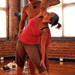 Hot Yoga Teacher Lou gives student Hazel an adjustment