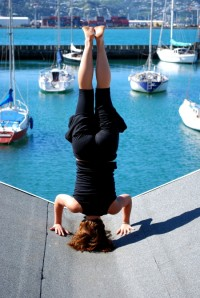 Lauren demonstrates headstand on a blue sky Wellington day