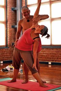 Hot Yoga Teacher Lou gives student Hazel an adjustment