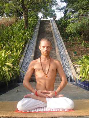 Shakti Mat creator Om Mokshananda sitting on the mat.