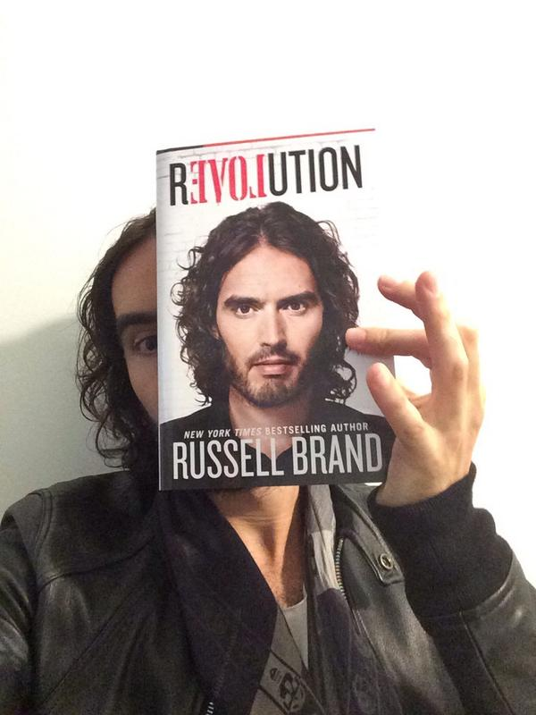 Russell Brand holding a copy of his book Revolution